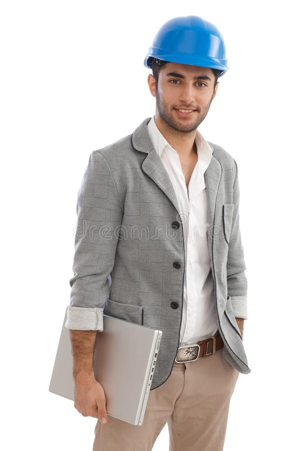 Młody architekta mienia laptopu ono uśmiecha się fotografia royalty free