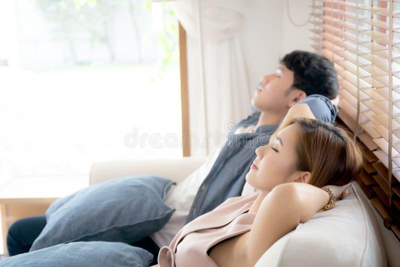 Młody asyjczyk uśmiecha się wygodnie na sofie w salonie w wakacjach, wypoczynek rodzinny i wypoczynek ze szczęścia fotografia stock