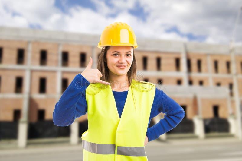 Młody atrakcyjny żeński architekt robi wywoławczemu gestowi zdjęcie stock