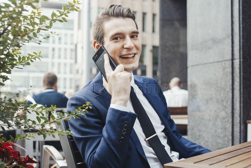Młody atrakcyjny biznesmen opowiada telefonem komórkowym i patrzeje widza zdjęcia royalty free