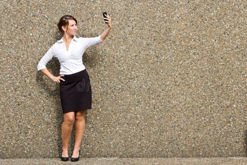 Młody atrakcyjny biznesowej kobiety kierownictwo używa jej mądrze telefon zdjęcie royalty free