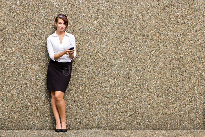 Młody atrakcyjny biznesowej kobiety kierownictwo używa jej mądrze telefon zdjęcia stock