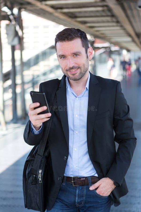Młody atrakcyjny biznesowy mężczyzna używa smartphone zdjęcia royalty free
