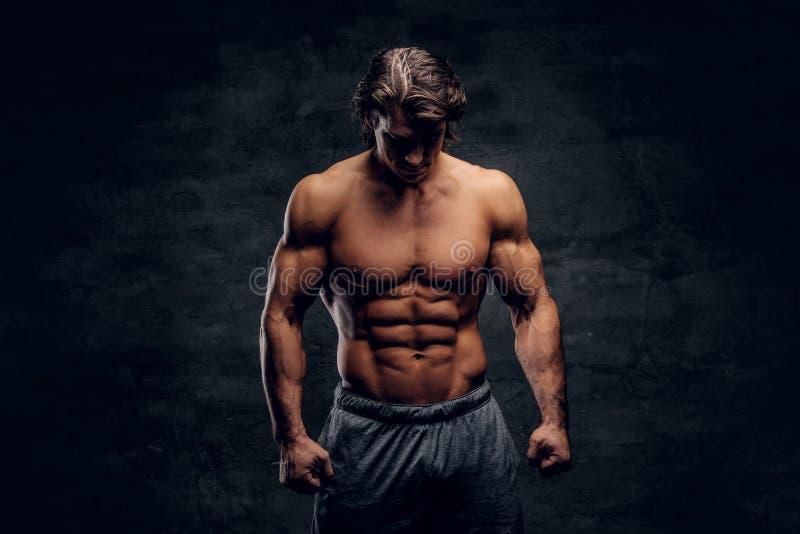 Młody atrakcyjny bodybuilder z nagą półpostacią pozuje dla fotografa zdjęcia royalty free