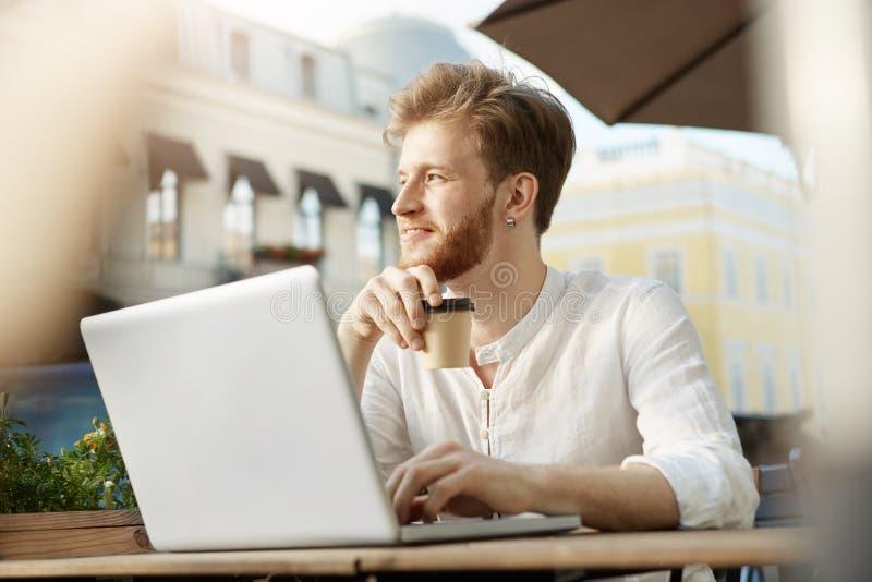 Młody atrakcyjny brodaty imbirowy facet z kolczykiem w białej koszula pije kawę, pracuje na nowym projekcie na jego daleko fotografia royalty free