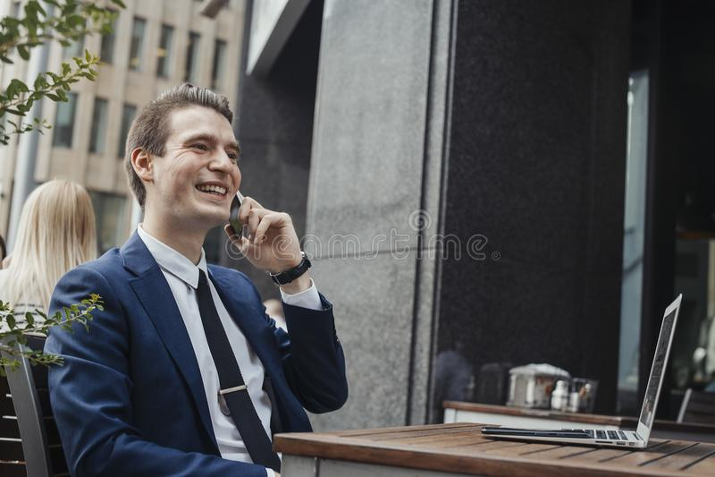 Młody atrakcyjny brunetka biznesmen opowiada telefonem komórkowym i ono uśmiecha się zdjęcia royalty free