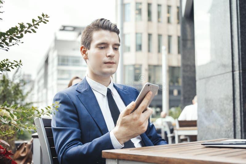 Młody atrakcyjny brunetka biznesmen patrzeje telefonu komórkowego ekran zdjęcia stock