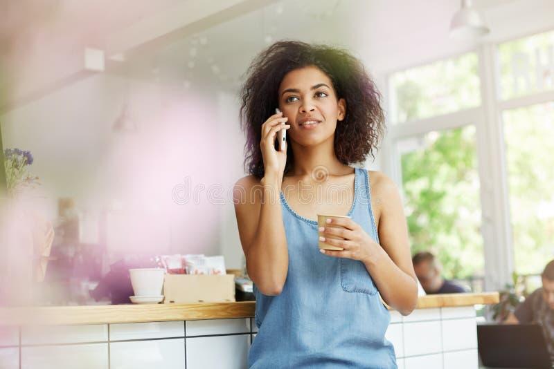 Młody atrakcyjny ciemnoskóry student uniwersytetu opowiada na telefonie z ona z ciemnym falistym włosy w przypadkowej błękitnej k zdjęcia royalty free