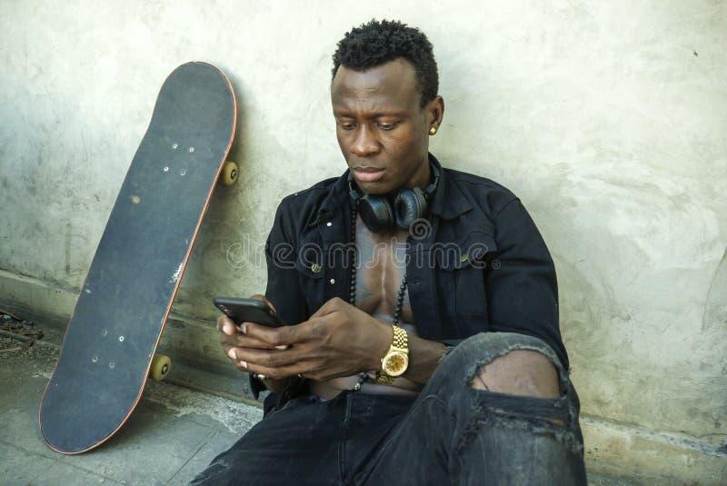 Młody atrakcyjny i poważny czarny afro Amerykański mężczyzny obsiadanie na grunge ulicy ziemi kącie z łyżwy deską w badass złej c zdjęcie stock