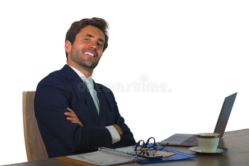 Młody atrakcyjny i skuteczny biznesowy mężczyzna pracuje przy biurowym laptopu biurkiem ufnym w ono uśmiecha się szczęśliwy w pom fotografia stock