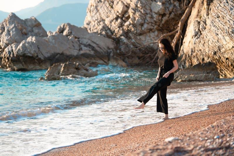 Młody atrakcyjny kobiety odprowadzenie na pogodnej plaży przy brzeg Podr??nik i blogger zdjęcia royalty free