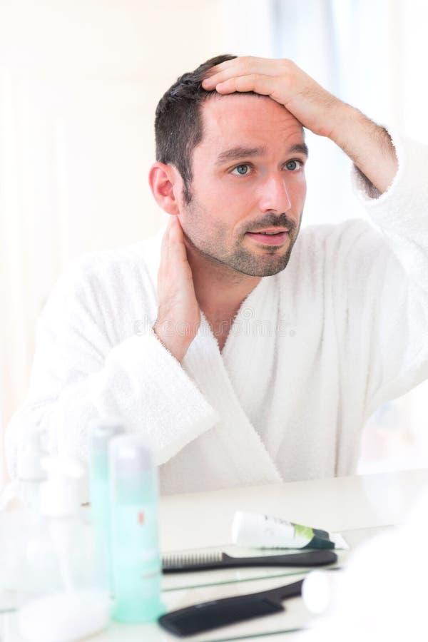 Młody atrakcyjny mężczyzna bierze opiekę jego włosy fotografia royalty free