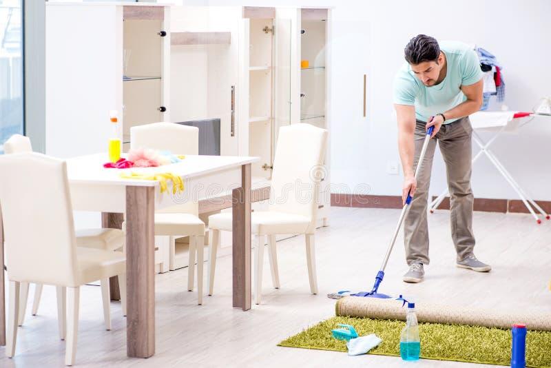 Młody atrakcyjny mężczyzna mąż robi mopping w domu obraz royalty free