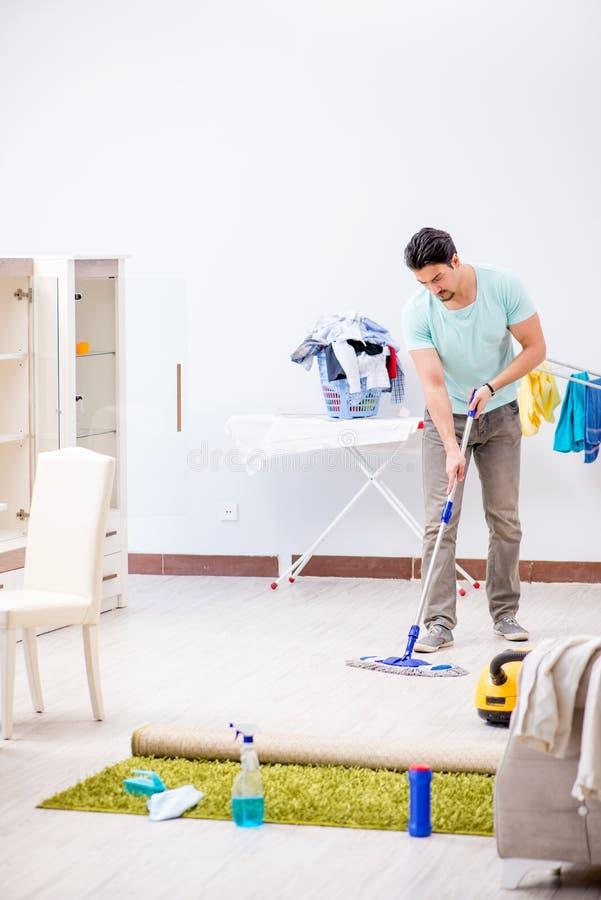 Młody atrakcyjny mężczyzna mąż robi mopping w domu obrazy stock