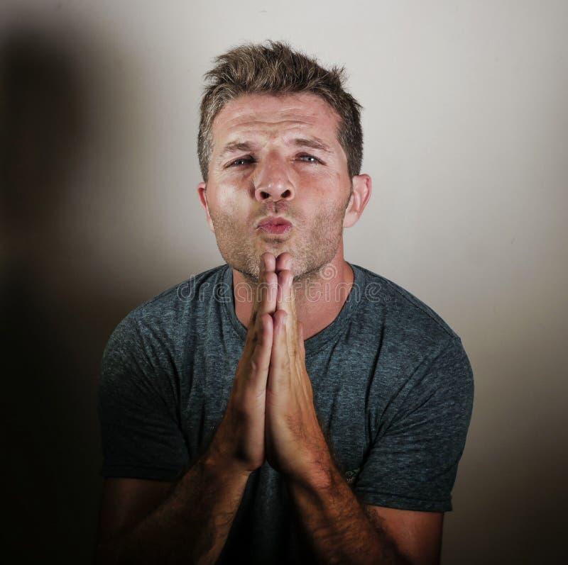 Młody atrakcyjny mężczyzna patrzeje niespokojny z rękami na jego usta błaga błagać i ono modli się tak jakby mieć nadzieję coś i  obrazy stock