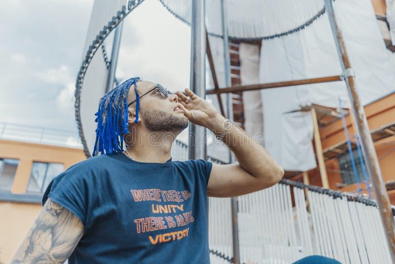 Młody atrakcyjny mężczyzna patrzeje słońce z błękitnymi dreadlocks Przez okularów przeciwsłonecznych obraz royalty free