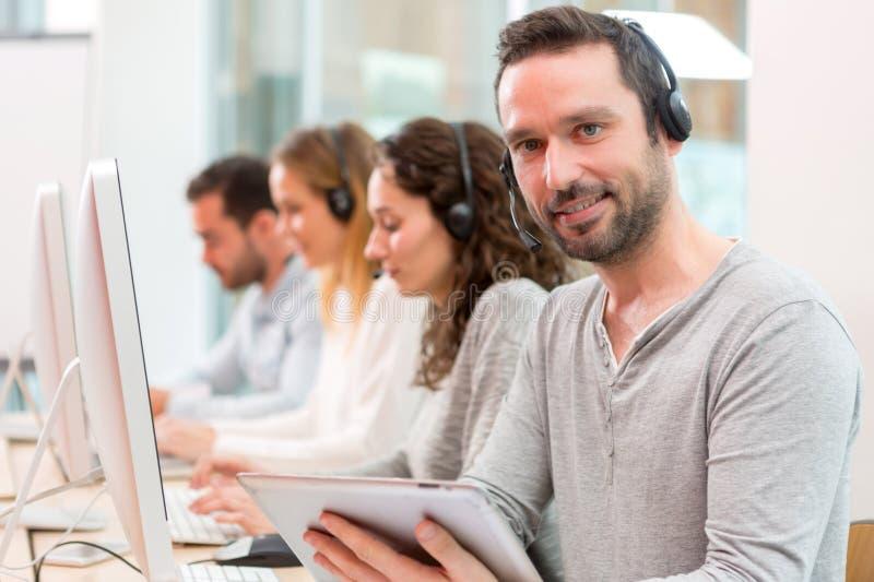Młody atrakcyjny mężczyzna pracuje w centrum telefonicznym fotografia stock