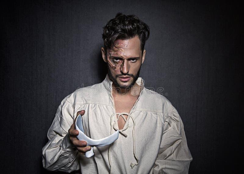 Młody atrakcyjny mężczyzna z twarzy bliznami i białą maską, ubierającą w fantomu opery spojrzenie fotografia royalty free