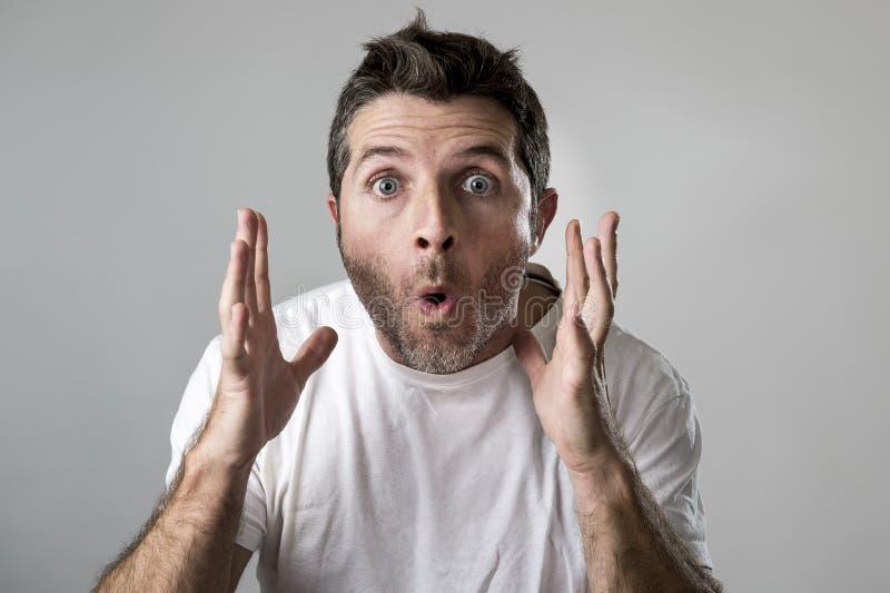 Młody atrakcyjny mężczyzna zdumiewał zadziwia w szok niespodzianki twarzy wyrażeniu i szok emoci zdjęcia stock