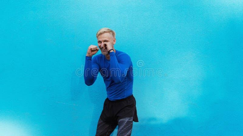 Młody atrakcyjny mężczyzny boks na błękitnym tle zdjęcia royalty free