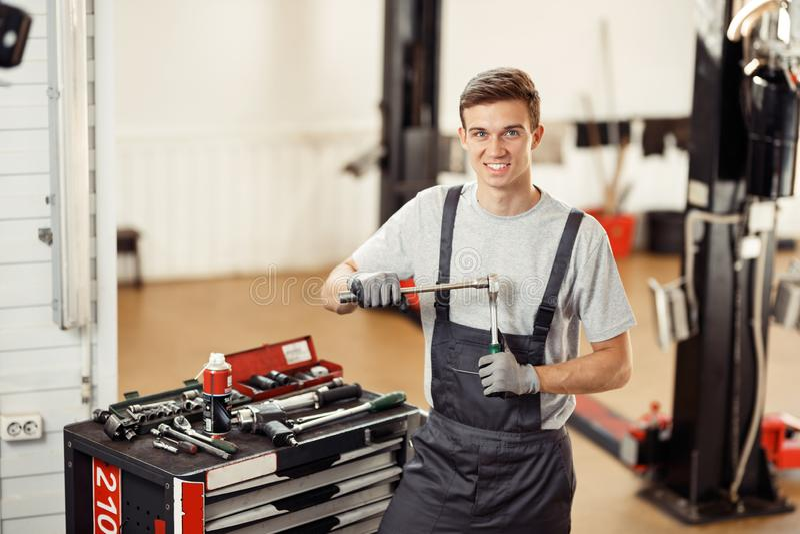 Młody atrakcyjny mechanik jest przy jego pracą podczas gdy przygotowywający dla naprawiać samochód zdjęcie royalty free