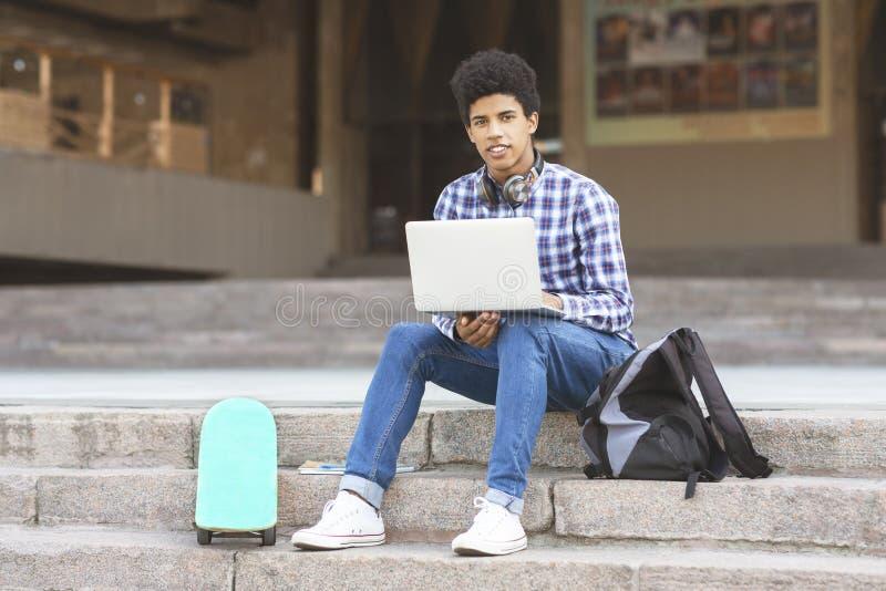 Młody atrakcyjny nastoletni studiujący outdoors używa laptop fotografia royalty free