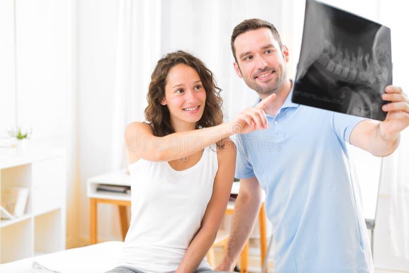 Młody atrakcyjny physiotherapist analizuje promieniowanie rentgenowskie z pacjentem zdjęcia royalty free