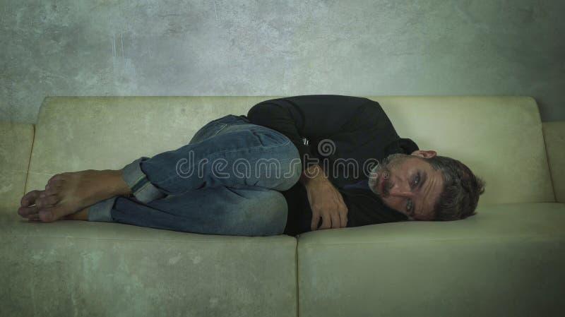 Młody atrakcyjny przygnębiony, smutny ciemniutki mężczyzna leżanki płacz gubjący w i w domu bólu i rozpacza cierpienia niepokoju  fotografia stock
