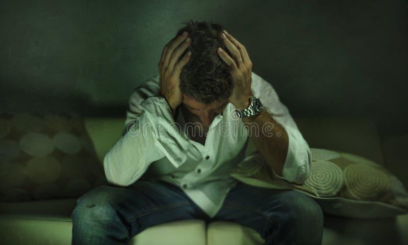 Młody atrakcyjny przygnębiony, smutny ciemniutki mężczyzna leżanki płacz gubjący w i w domu bólu i rozpacza cierpienia niepokoju  obrazy royalty free