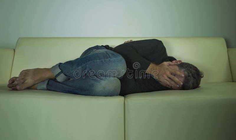 Młody atrakcyjny przygnębiony, smutny ciemniutki mężczyzna leżanki płacz gubjący w i w domu bólu i rozpacza cierpienia niepokoju  zdjęcie stock