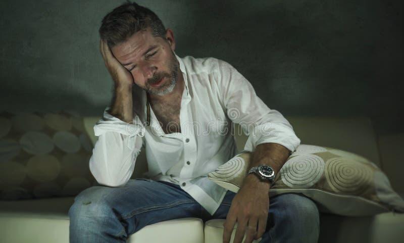 Młody atrakcyjny przygnębiony, smutny ciemniutki mężczyzna leżanki płacz gubjący w i w domu bólu i rozpacza cierpienia niepokoju  obraz stock