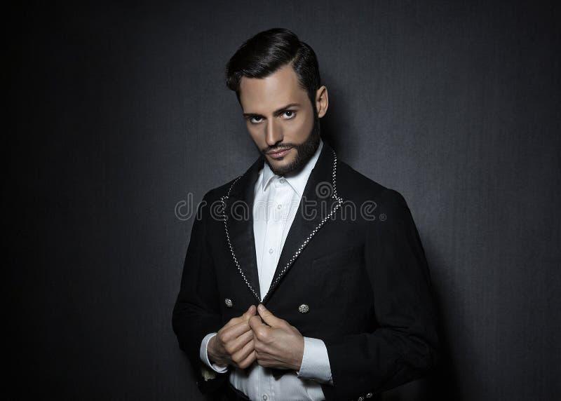 Młody atrakcyjny, seksowny mężczyzna z brodą, ubierającą w cyrkowej spojrzenie kurtce zdjęcie stock