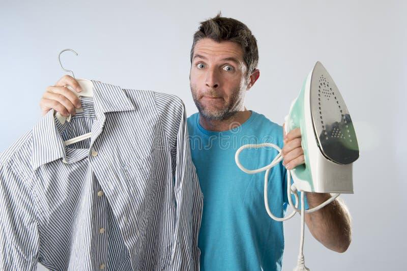 Młody atrakcyjny, sfrustowany mężczyzna mienia żelazo i i męczący w zanudzającej i gnuśnej twarzy fotografia stock