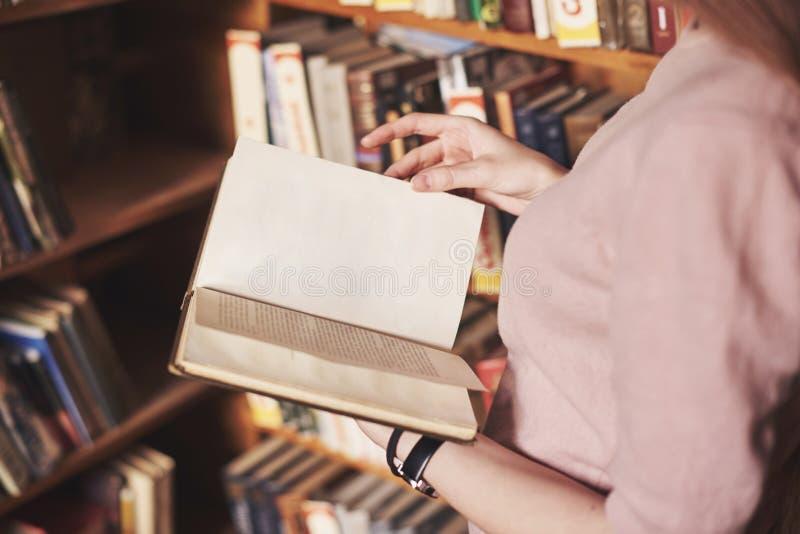 Młody atrakcyjny studencki bibliotekarski czytanie książka między bibliotecznymi półkami na książki zdjęcie royalty free