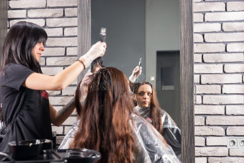 Młody atrakcyjny stylista podczas procesu barwiarstwo włosy kobieta obrazy stock