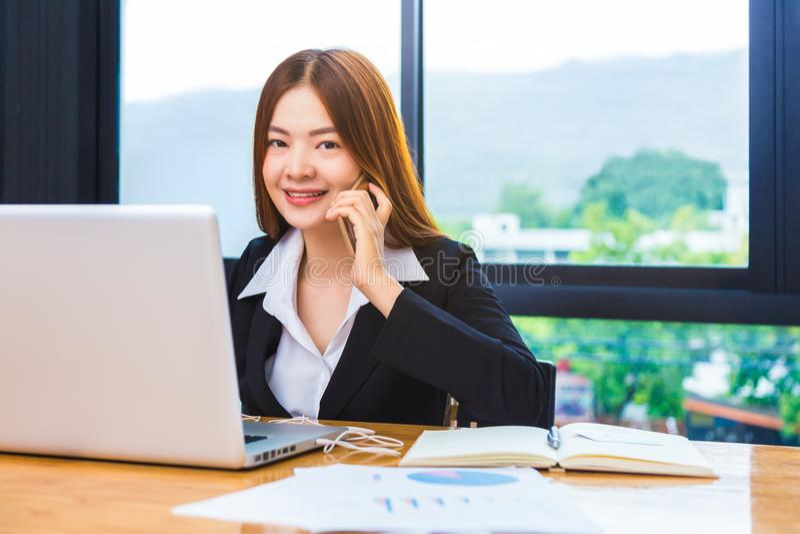 Młody atrakcyjny szczęśliwy azjatykci bizneswoman używa jej w i telefon zdjęcie royalty free
