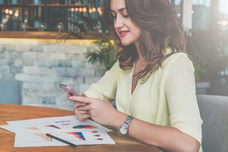 Młody atrakcyjny uśmiechnięty bizneswomanu obsiadanie w kawiarni przy stołem, używać smartphone i patrzejący jego ekran zdjęcia stock