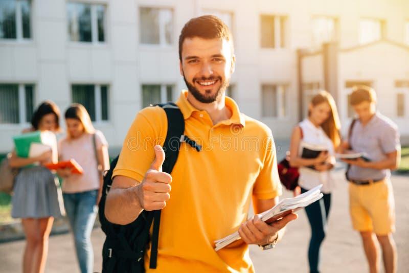 Młody atrakcyjny uśmiechnięty studencki pokazuje kciuk w górę outdoors na kampusie przy uniwersytetem zdjęcie royalty free