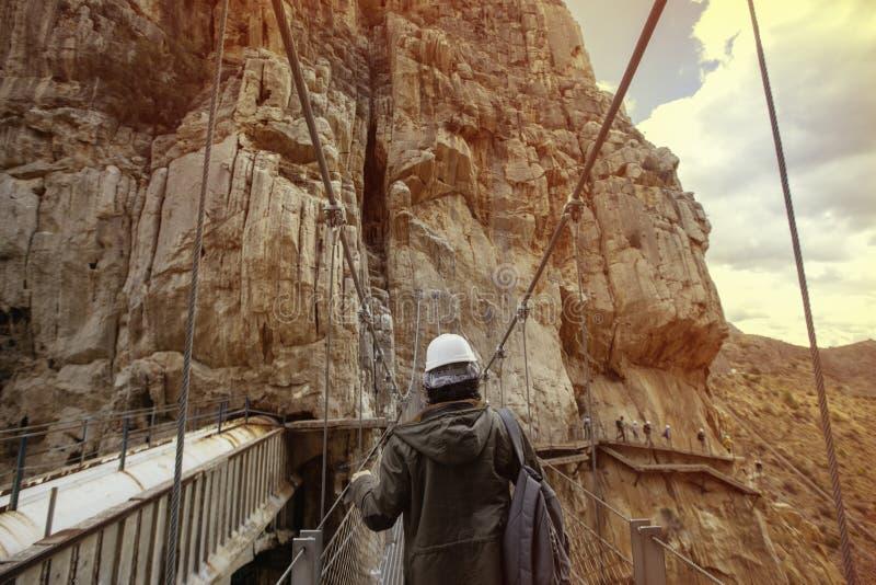 Młody awanturniczy mężczyzna krzyżuje drewnianego most z hełmem zdjęcie royalty free