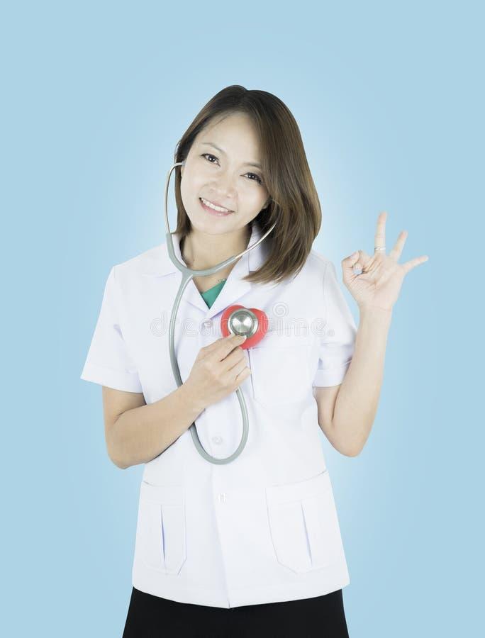 Młody azjata lekarki stojak trzyma czerwonego serce w jej ręce z smiley twarzą zdjęcia stock