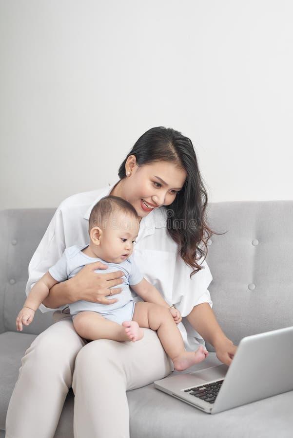 Młody azjata matki obsiadanie na kanapie z komputerem i jej córką w domu obrazy stock