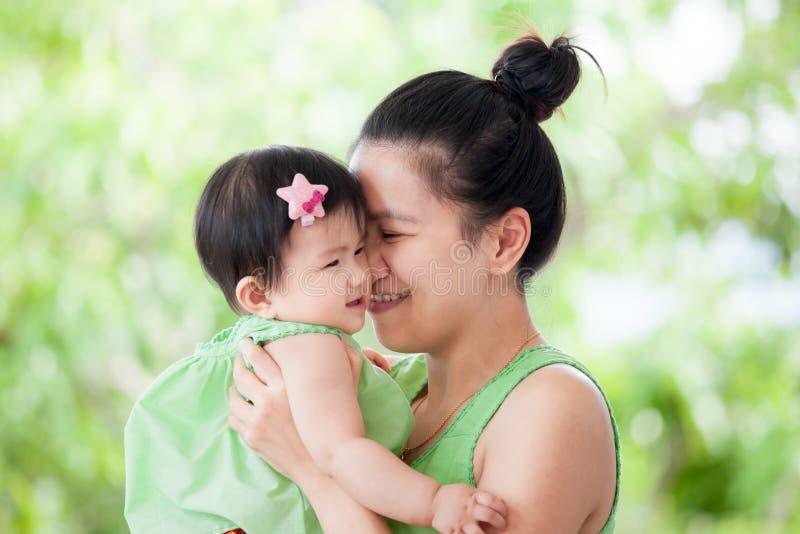 Młody azjata matki przewożenie i całowanie jej córka zdjęcia stock