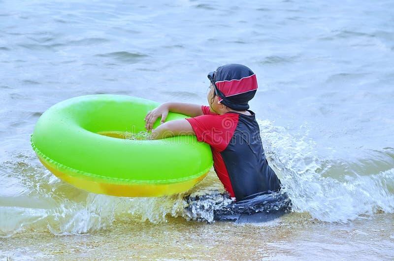 Młody azjata siedzi w kipieli na ocean plaży z jej pączkiem obraz stock