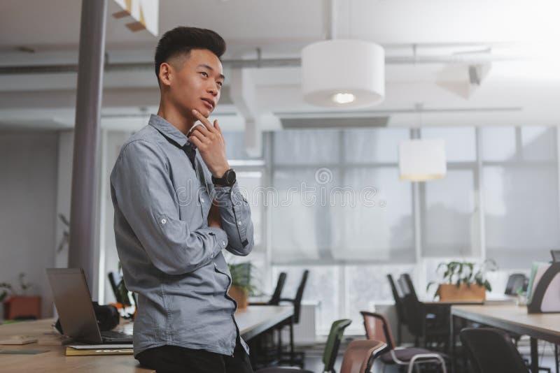 Młody Azjatycki biznesmen pracuje przy biurem zdjęcie stock