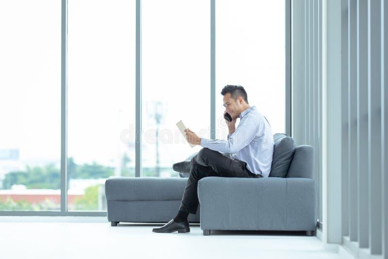 Młody Azjatycki biznesmen używa telefonu komórkowego obsiadanie na kanapie Happ zdjęcia stock