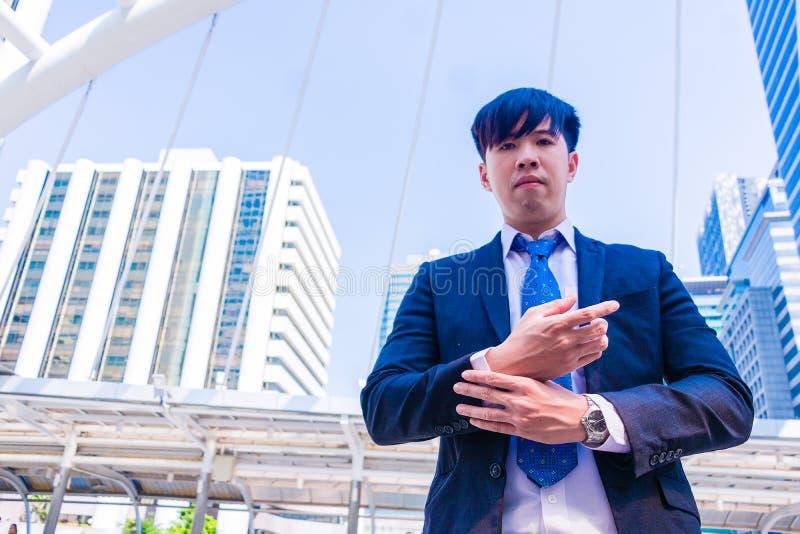 Młody Azjatycki biznesmen w miasteczku biznesmen widzii zegarek obraz stock