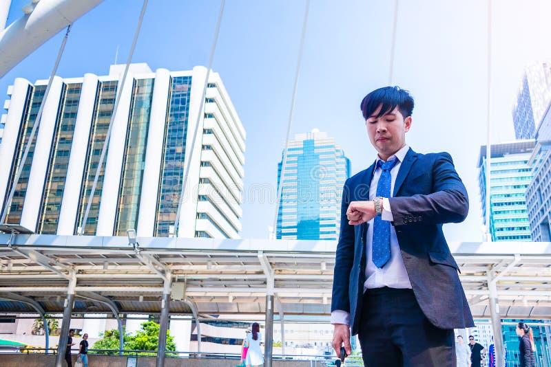 Młody Azjatycki biznesmen w miasteczku biznesmen widzii zegarek zdjęcia stock