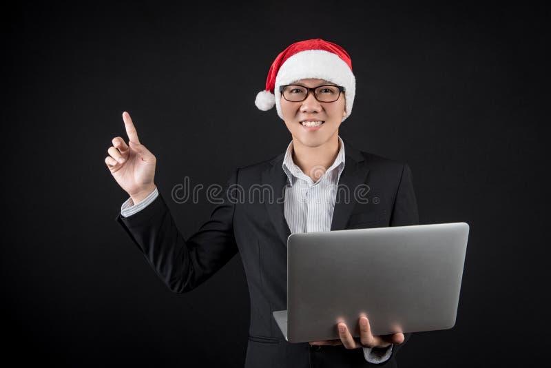 Młody Azjatycki biznesmen z Santa kapeluszowym używa laptopem zdjęcia stock