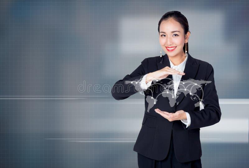 Młody Azjatycki bizneswoman trzyma kulę ziemską z ogólnospołeczną siecią obrazy stock