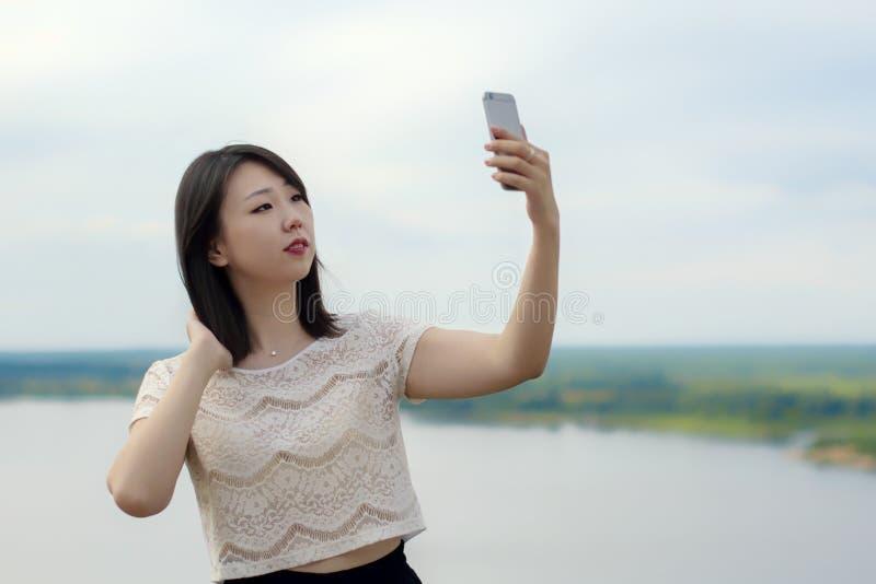 Młody Azjatycki dziewczyna uczeń bierze selfie w naturze w lecie na górze przeciw niebu obrazy royalty free